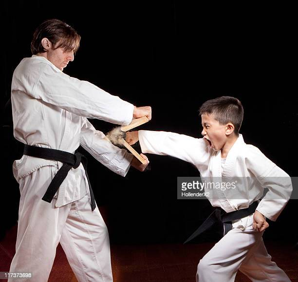 boy in karate outfit punching and breaking wood