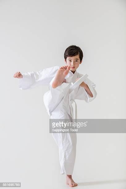 Boy In Karate Uniform Kicking