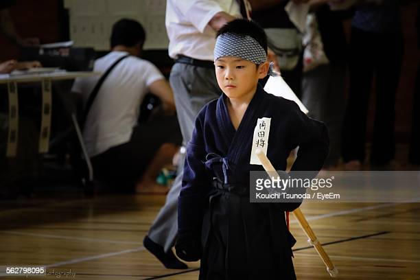 Boy In Kendo Uniform Looking Down While Standing On Floor
