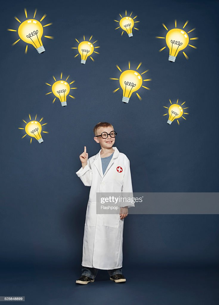 Boy in lab coat with cartoon lightbulbs : Stock Photo