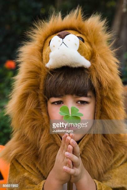 boy in lion costume with leaf - 4 leaf clover stock-fotos und bilder