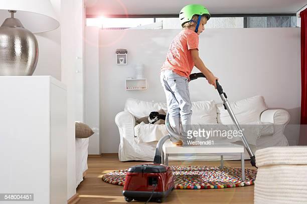 Boy in living room hoovering