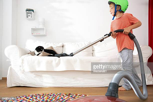 Boy in living room hoovering the sofa with cat