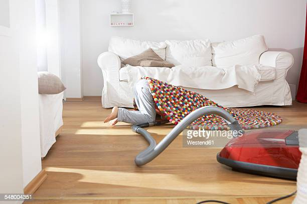 Boy in living room hoovering under carpet