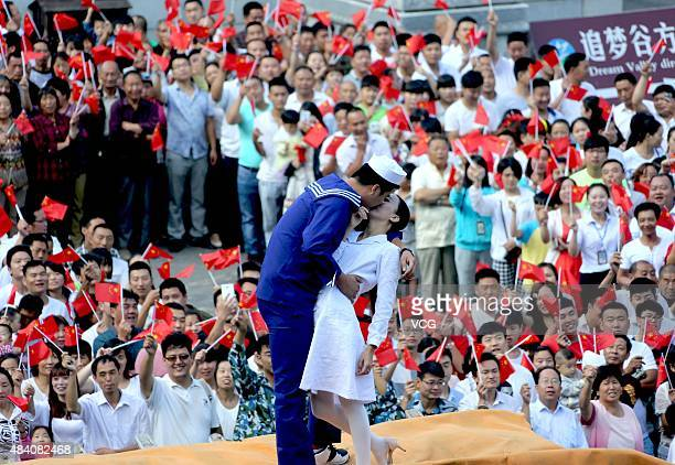 A boy in marine outfit and a girl in white dress kiss on a excavator at square of Laojun Mountain on August 15 2015 in Luoyang Henan Province of...