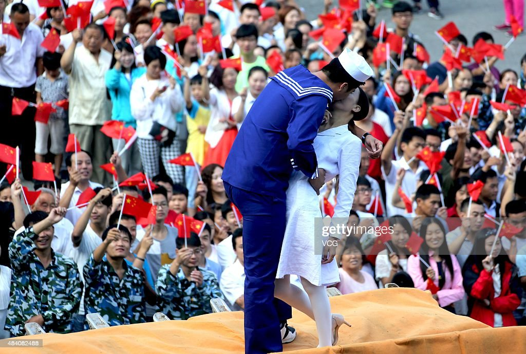 A boy in marine outfit and a girl in white dress kiss on a excavator at square of Laojun Mountain on August 15, 2015 in Luoyang, Henan Province of China. Aiming to celebrate the 70th anniversary of the victory of Anti-Japanese War, two young people in mariniere and white dress respectively kissed each other which reappeared the famous 'Victory Kiss' and other citizens coalesced a giant word '70'. 'Victory Kiss' (or V-J Day) is a photograph by Alfred Eisenstaedt that portrays an American sailor kissing a woman in a white dress on Victory over Japan Day in Times Square in New York City, on August 14, 1945.