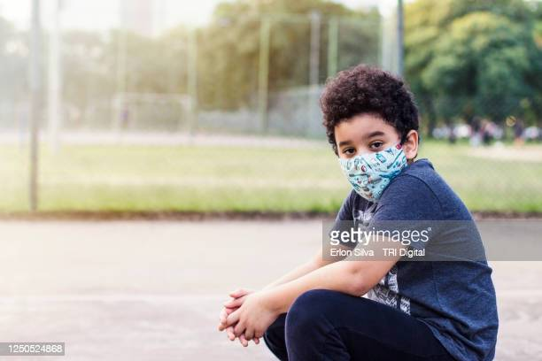 boy in mask enjoying the sun in the park to relieve quarantine times - bronzage masque photos et images de collection