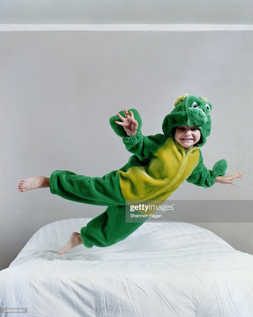Boy (4-6) in monster costume jumping on bed : Stockfoto