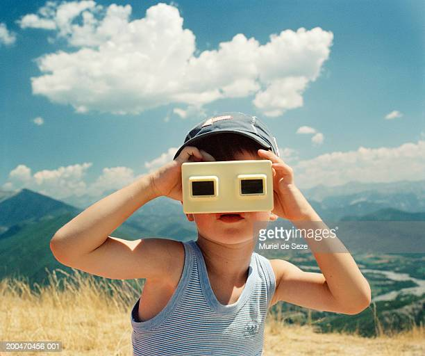 Boy (5-7) in mountainous landscape using slide viewer