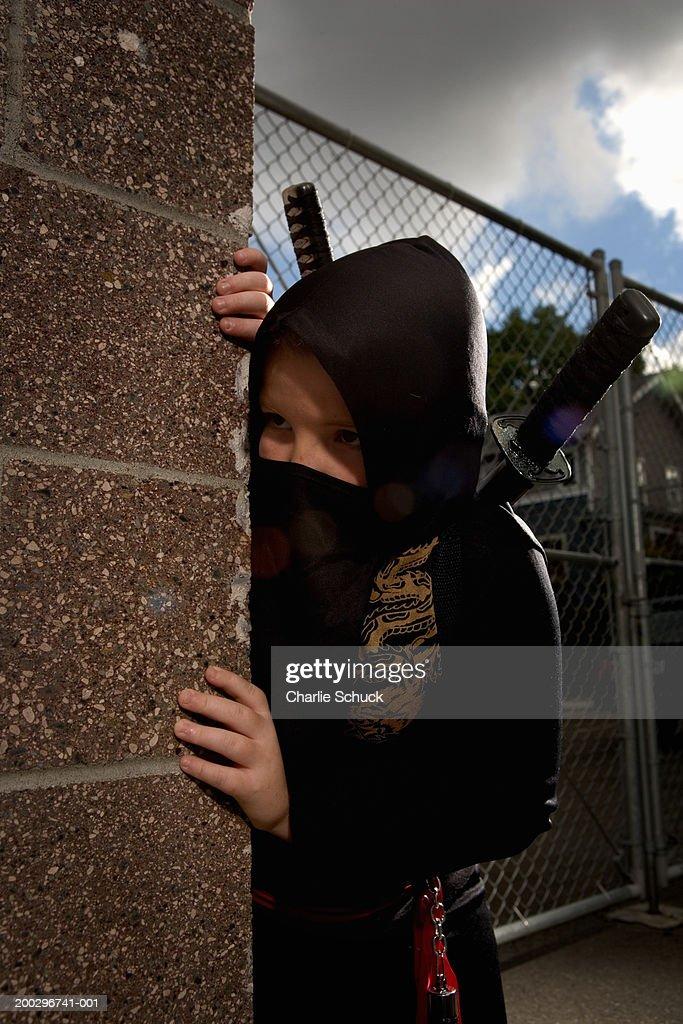 Boy (9-11) in Ninja costume, looking around corner of building : Stock Photo