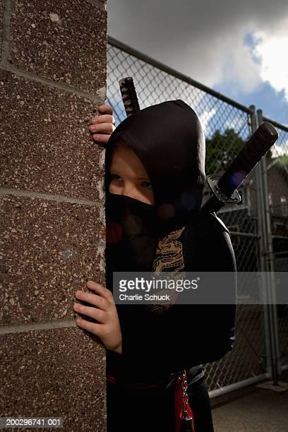 Boy (9-11) in Ninja costume, looking around corner of building