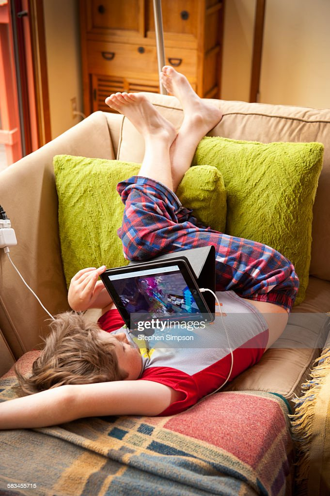 boy in pajamas on couch with tablet : Stock Photo