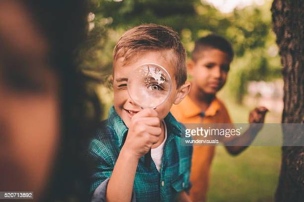 boy in park holding a magnifying glass to his eye - curiosity stock pictures, royalty-free photos & images