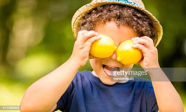 Junge im park holding Zitronen wie Augen