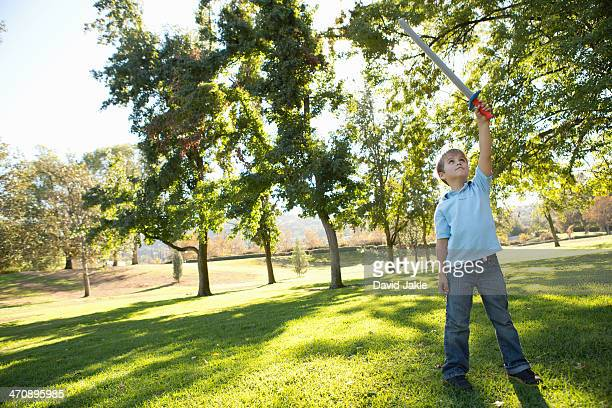 Boy in park raising toy sword in air