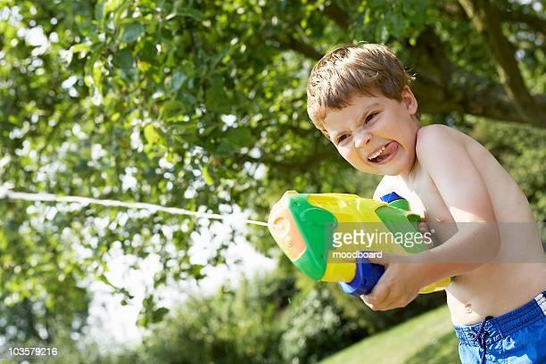 Boy in park shooting pump action water pistol