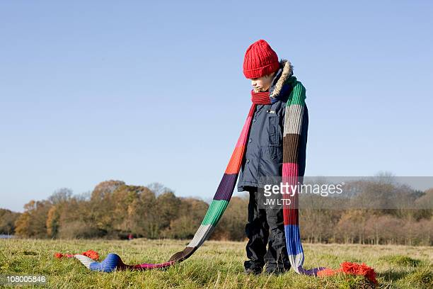 boy in park wearing long knitted scarf - jumper stock pictures, royalty-free photos & images