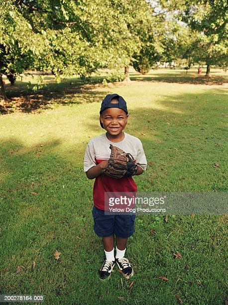 Boy (5-7) in park with baseball glove grinning, portrait