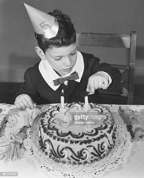 Boy (2-3) in party hat lighting candle on birthday cake, (B&W), elevated view