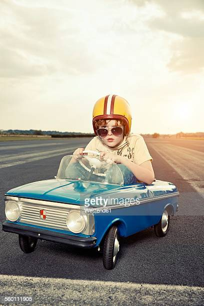 Boy in pedal car on race track