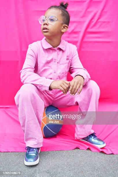boy in pink coveralls sitting on basketball - one boy only stock pictures, royalty-free photos & images