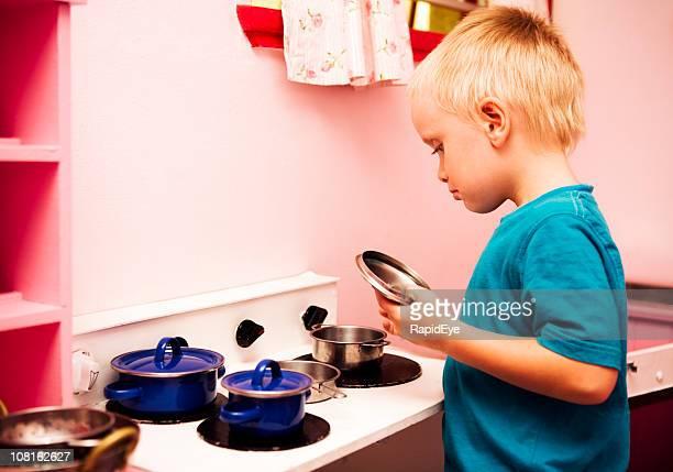 Boy in play kitchen