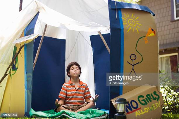 Boy in playhouse meditating