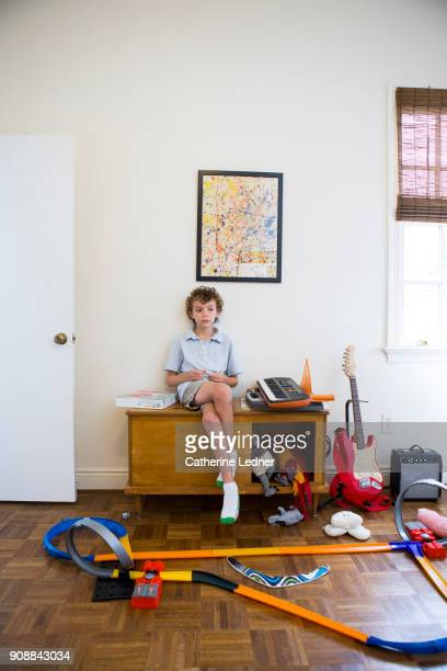 Boy in playroom with parquet floors pondering his racetrack in the foreground