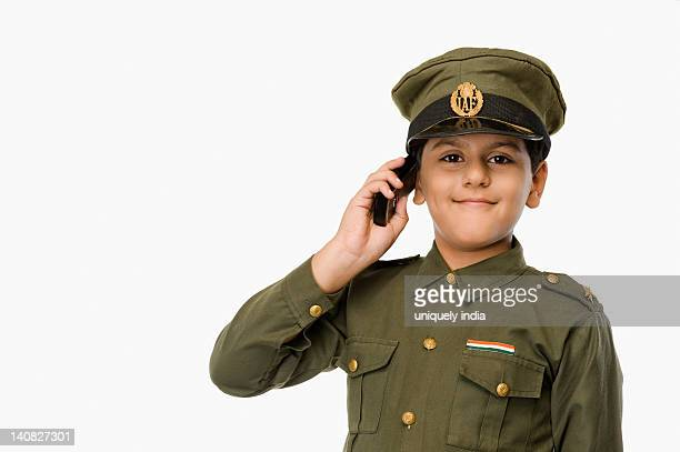 Boy in police uniform talking on a mobile phone