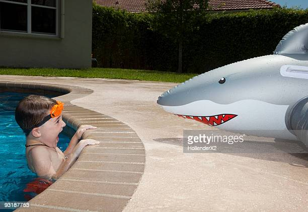 boy in pool with blow up shark