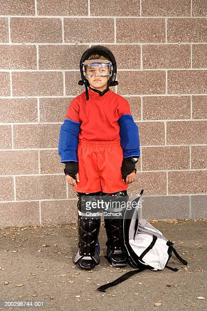Boy (8-10) in protective gear with school backpack, portrait.