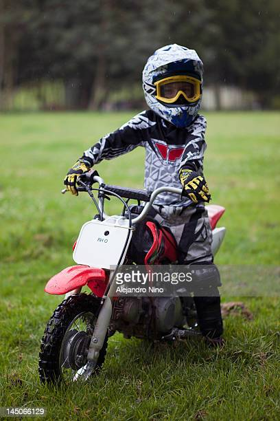 a boy in protective sportswear sitting on a dirt bike - only boys photos stock photos and pictures