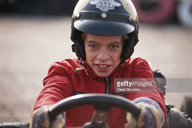 Boy (10-11) in race car, smiling, close-up