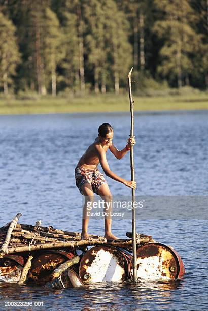 Boy (10-11) in raft, holding bamboo