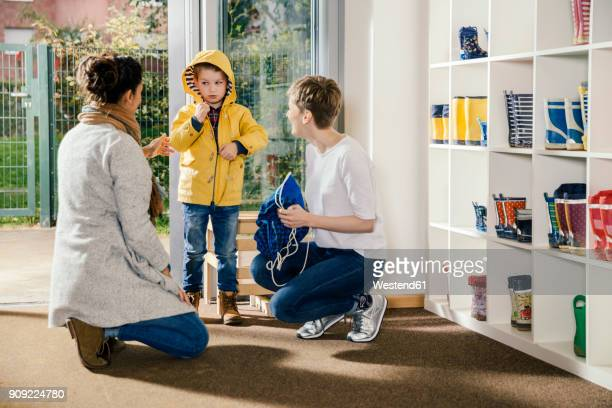 Boy in raincoat with mother and pre-school teacher in kindergarten