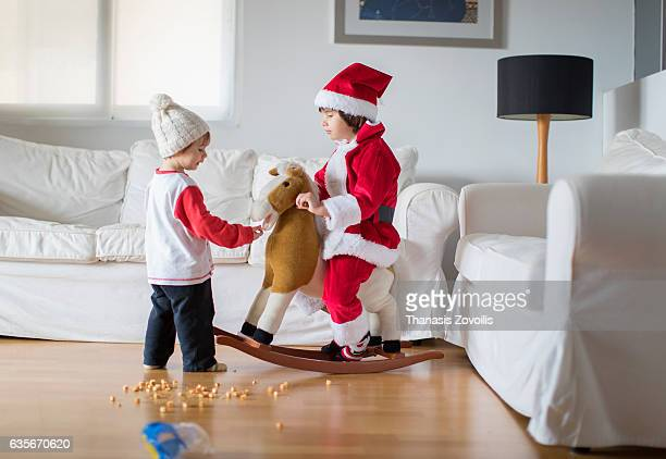 Boy in red Santa Claus costume sits on a toy horse