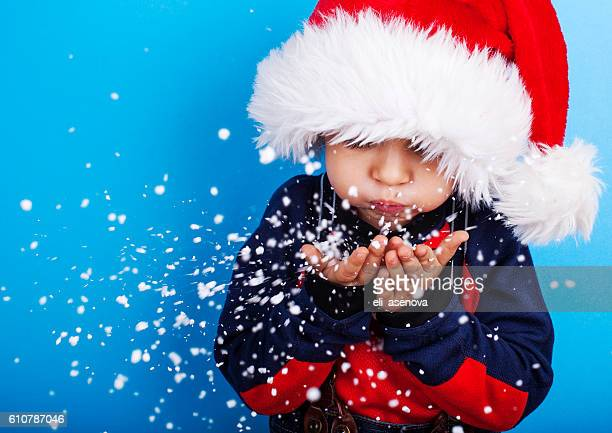 Boy in santa claus hat blowing snowflakes
