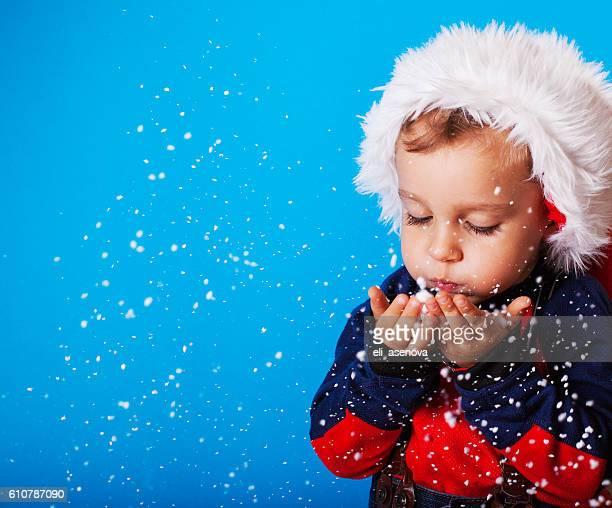 Junge in santa claus Hut Blasen Schneeflocken