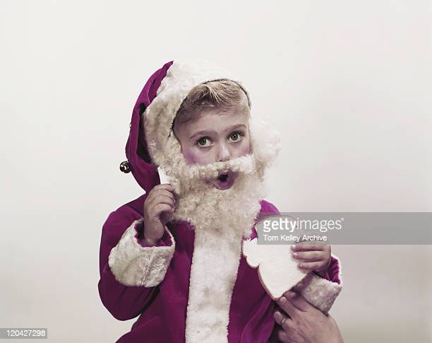 Boy in santa costume holding bread, portrait