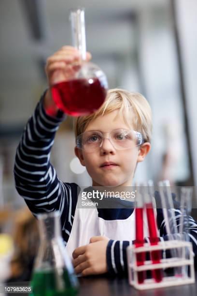 boy in school laboratory - frasco cónico fotografías e imágenes de stock