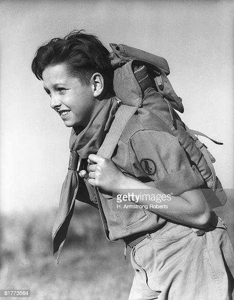 boy in scout uniform, carrying backpack. (photo by h. armstrong roberts/retrofile/getty images) - pfadfinder stock-fotos und bilder