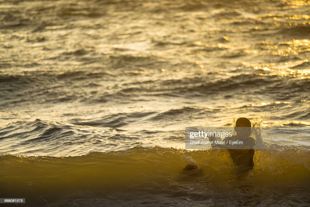 Boy In Sea During Sunset : Stock Photo