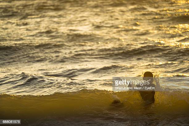 Boy In Sea During Sunset