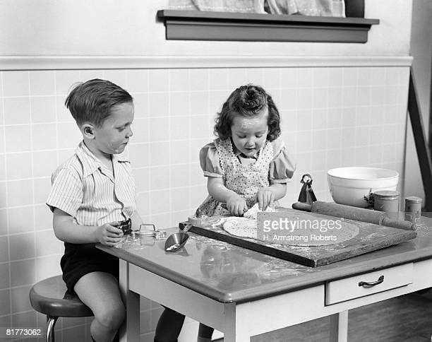boy in shirt & shorts sitting at table watching standing girl in print apron over dress preparing cookie dough flour rolling pin molds baking kitchen. - 40s pin up girls stockfoto's en -beelden