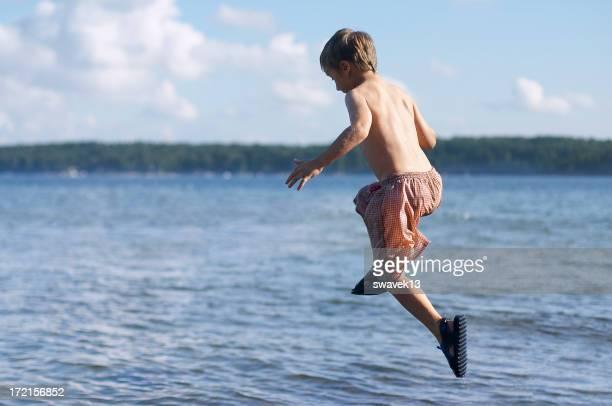 Boy in shorts jumping mid-air into lake