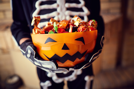 Boy in skeleton costume holding bowl full of candies 615726970