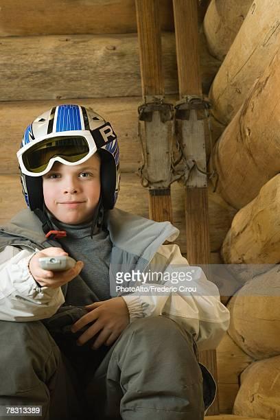 Boy in ski gear pointing remote control at camera