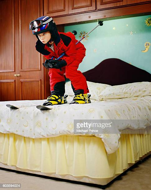 Boy in Ski Pose on Bed