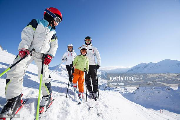 boy in skiing outfit with his family