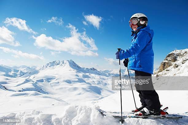Boy in skis on snowy mountaintop